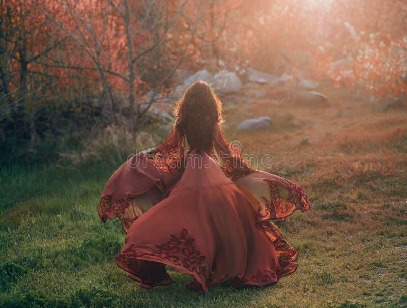 Девушка брюнет с волнистыми, толстыми волосами бежит к встрече солнца Фото от задней части, без стороны Она имеет l стоковые фотографии rf
