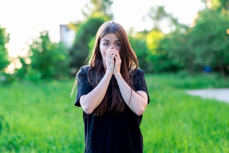 Девушка брюнет с длинными волосами лета в природе в черной футболке Руки покрывая его рот Эмоционально, страх a стоковое изображение