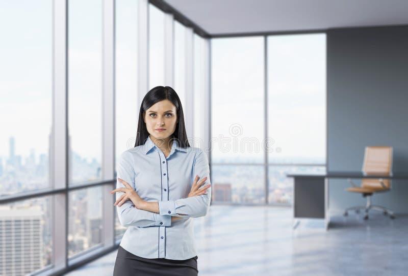 Девушка брюнет с пересеченными руками стоит в угловом панорамном офисе стоковое фото rf