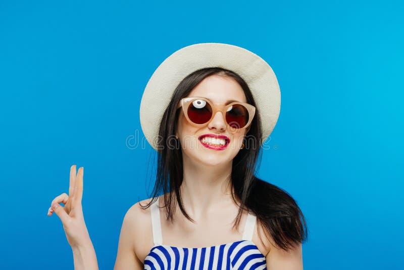 Девушка брюнет с солнечными очками и шляпой на голубой предпосылке стоковые изображения