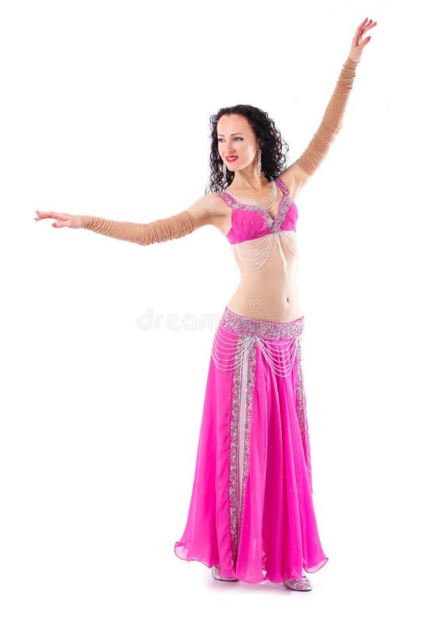 Девушка брюнет танцора с длинными волосами в красном восточном костюме представляя и танцуя стоковые изображения