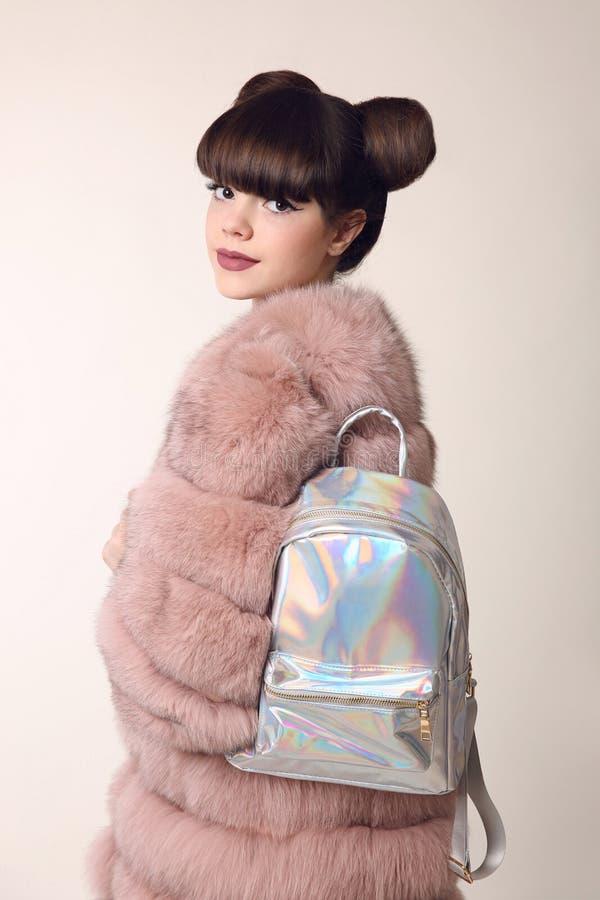Девушка брюнет усмехаясь предназначенная для подростков в розовой меховой шыбе рекламирует рюкзак, стоковое изображение rf