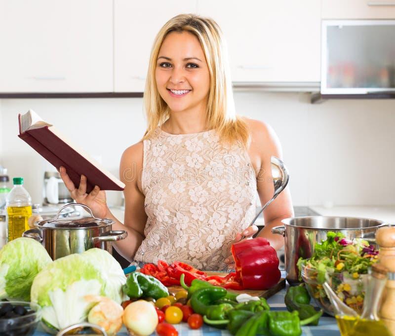 Девушка варя с veggies дома стоковые изображения