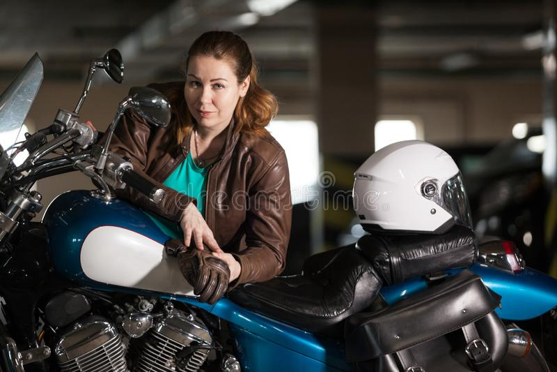 Девушка велосипедиста в кожаной куртке представляя на мотоцикле в парковке, голубом мотоцикле и белом шлеме стоковое фото rf