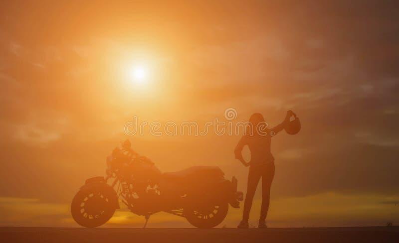 Девушка велосипедиста и классический мотоцикл на заходе солнца стоковое фото rf