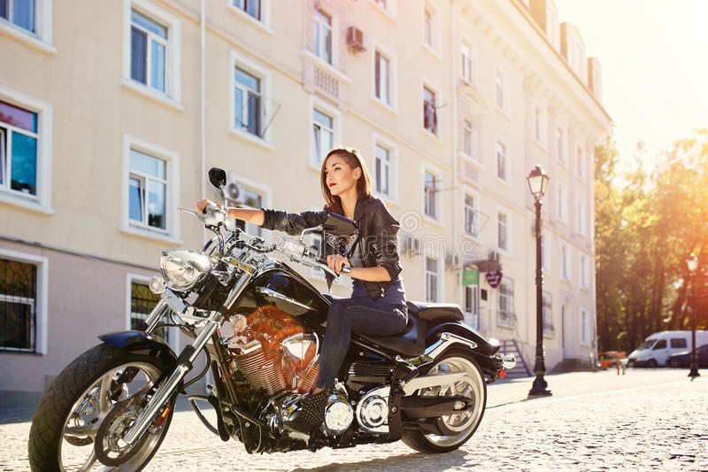 Девушка велосипедиста в кожаной куртке ехать мотоцикл стоковая фотография rf