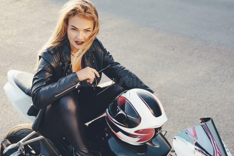 Девушка велосипедиста в коже одевает на мотоцикле стоковое изображение