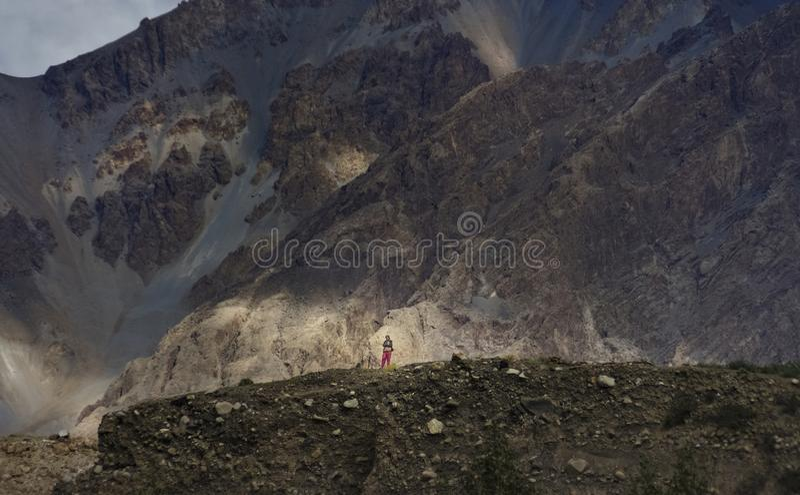 Девушка взбираясь горы вокруг деревни для того чтобы заметить возвращение людей от гор стоковые фотографии rf