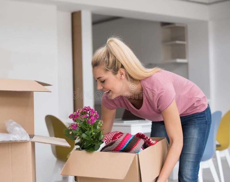 Девушка двигая в новую квартиру стоковые фото