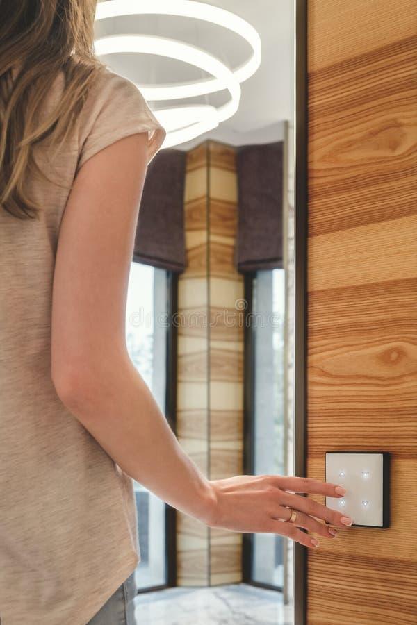 Девушка включает светлые прессы на переключателе касания стоковые изображения rf