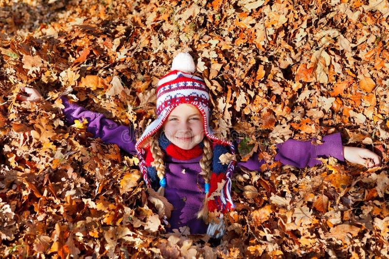 Девушка внутри листьев осени стоковое фото