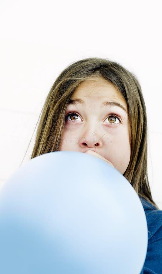 девушка воздушного шара дуя стоковое изображение