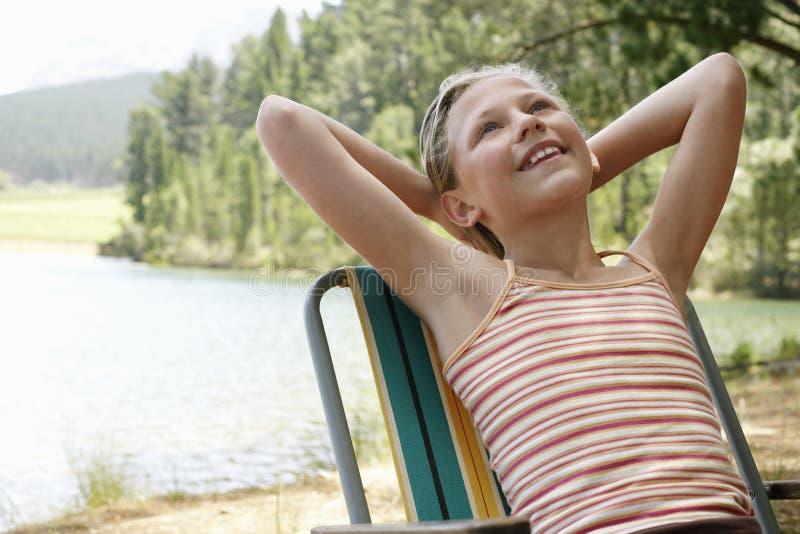 Девушка возлежа на Deckchair озером стоковые фотографии rf