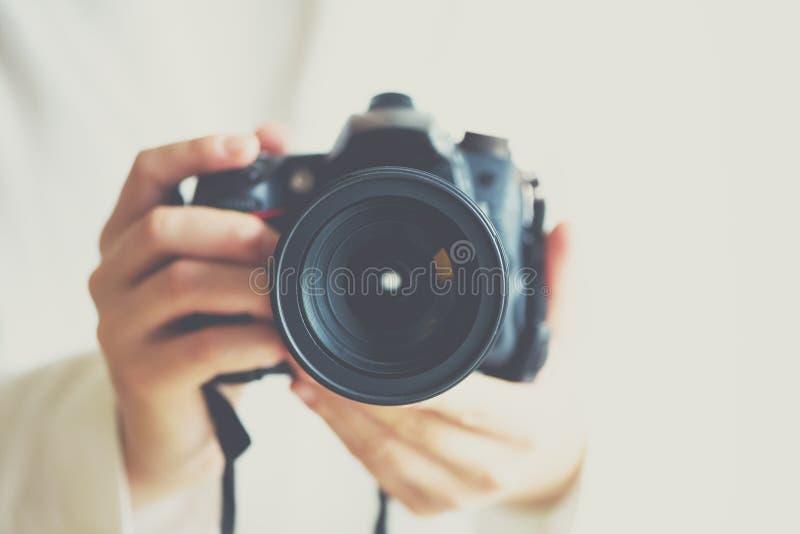 Девушка вручает держать камеру фото с винтажным влиянием цвета, белой предпосылкой, космосом экземпляра стоковое изображение