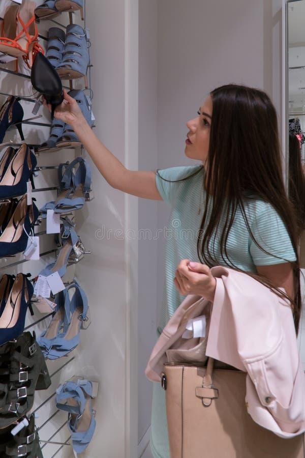 Девушка выбирает ее ботинки Девушка не знает чего выбрать стоковое фото rf