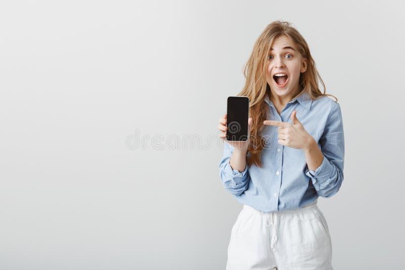 Девушка выиграла smartphone в лотереи Портрет изумленной очаровательной молодой женщины в голубой блузке показывая smartphone и у стоковые фото
