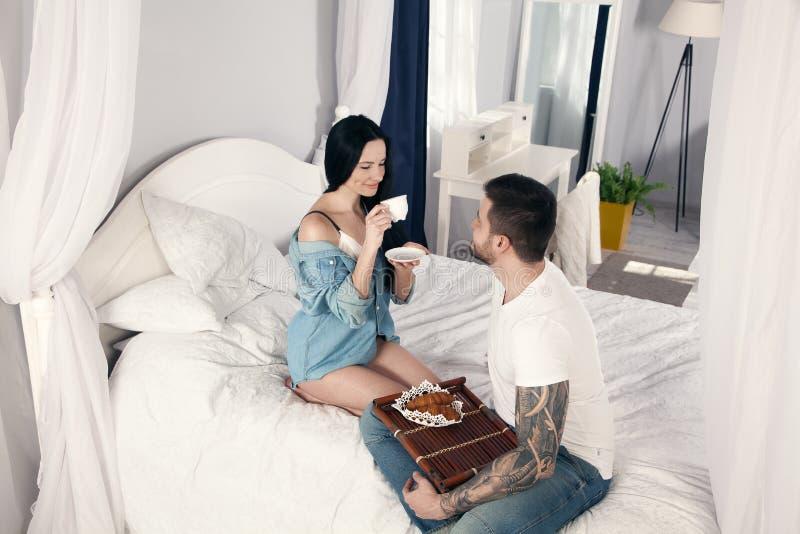 Девушка выпивает кофе утра, который ее любимый супруг принесенный к кровати они очень счастливы стоковые фото