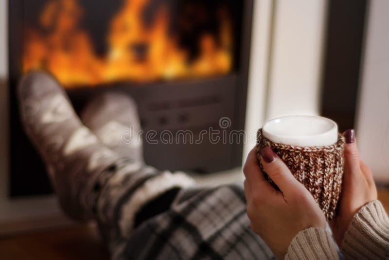Девушка выпивая горячий чай перед камином и грея ноги стоковые фото