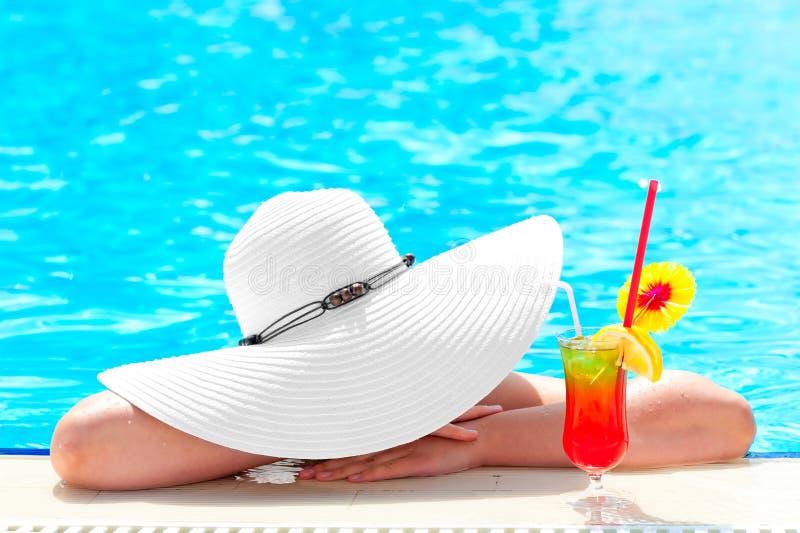 Девушка в бассейне с коктеилем ослабляет стоковое изображение