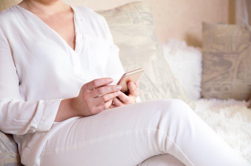 Девушка в белизне держит телефон в его руках Прочитайте новости на телефоне Человек с телефоном в его руках стоковая фотография