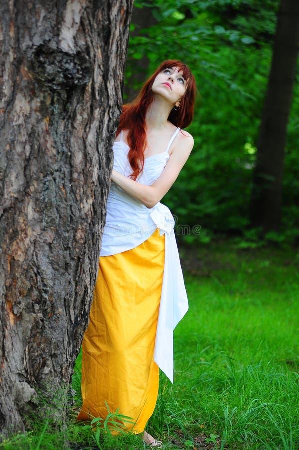Девушка в белизне с желтым выравниваясь платьем деревом стоковое фото rf