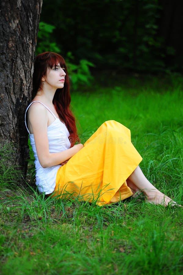 Девушка в белизне с желтым выравниваясь платьем деревом стоковые фото