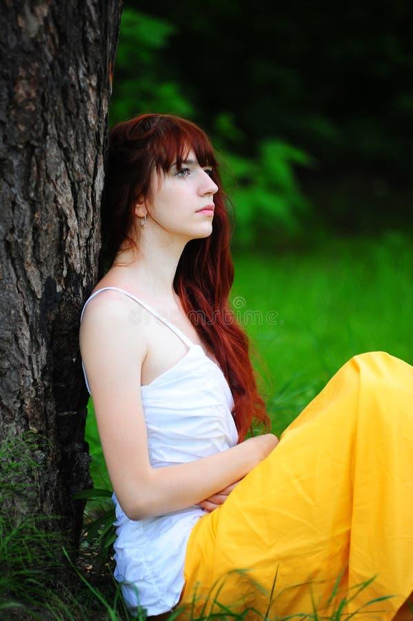 Девушка в белизне с желтым выравниваясь платьем деревом стоковые изображения