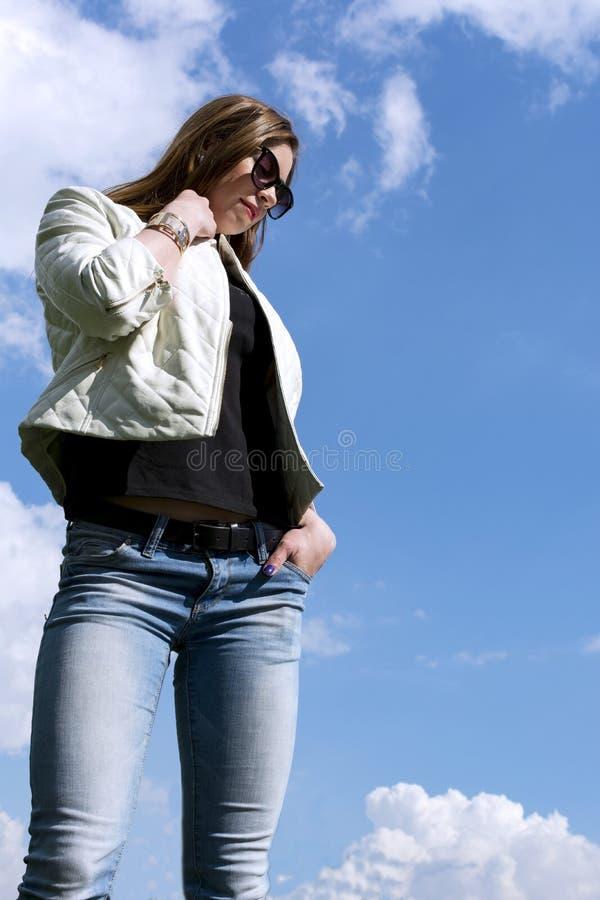 Девушка в белой кожаной куртке и джинсах на предпосылке sk стоковое фото rf