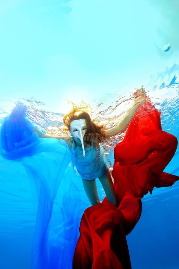 Девушка в белой маске с длинным носом плавает underwater и игры с красными и голубыми тканями стоковые изображения rf