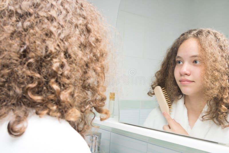 Девушка в белом купальном халате в положении bathroom перед зеркалом расчесывая ее вьющиеся волосы стоковая фотография