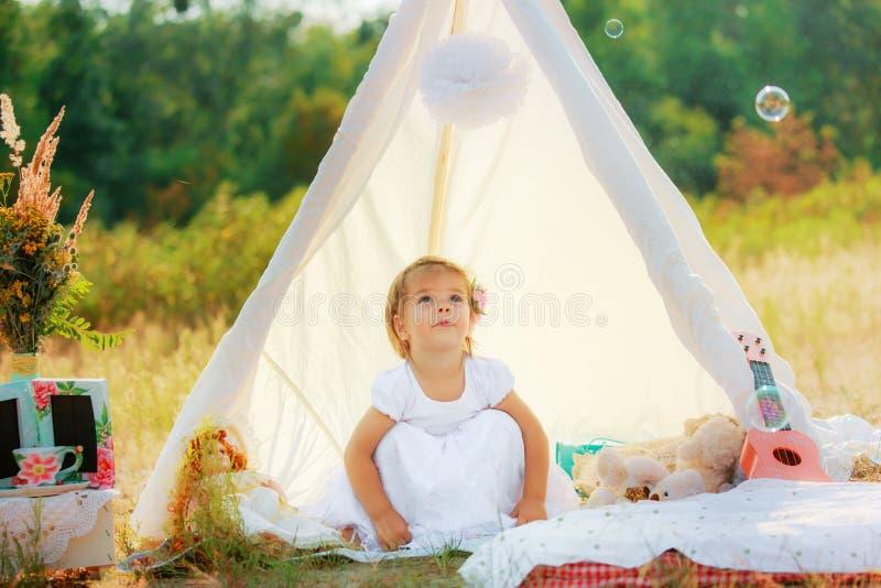 Девушка в белом платье сидит в белом шатре на предпосылке зеленых кустов Ребенок сидеть на его haunches стоковое фото rf