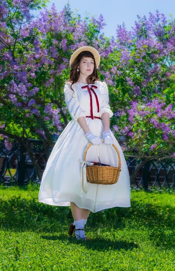 Девушка с корзиной в ее руках в прогулке в саде стоковые изображения