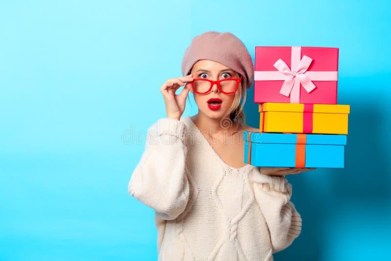 Девушка в белом свитере с коробками подарка покрашенными стоковые фотографии rf