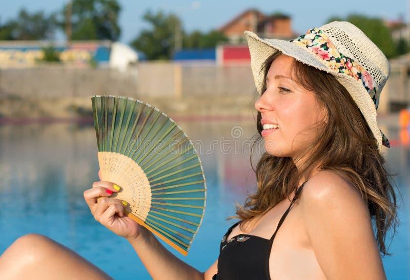 Девушка в бикини держа вентилятор руки бассейном стоковая фотография rf