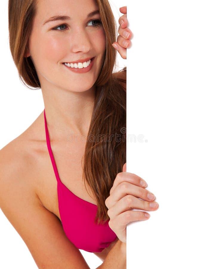 Девушка в бикини за пустым белым знаком стоковое изображение rf