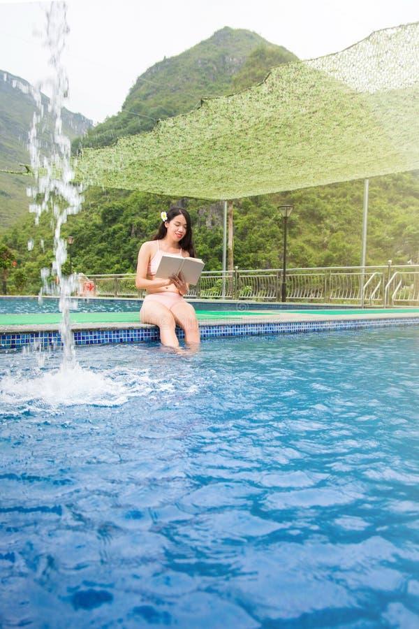 Девушка в бикини читая книгу бассейном стоковое фото