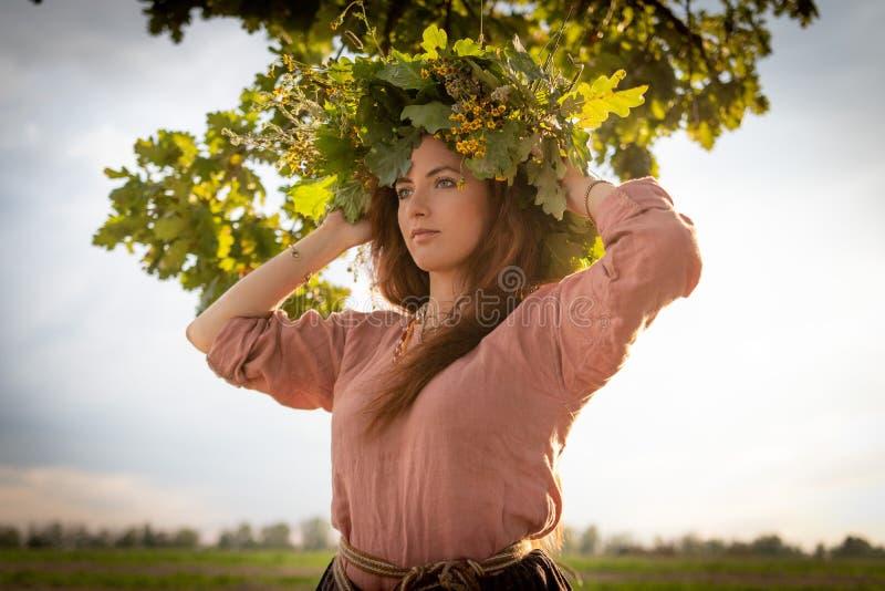 Девушка в венке листьев и цветков дуба под дубом стоковое изображение