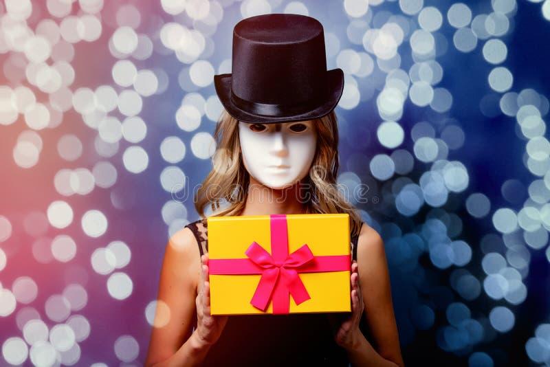 Девушка в верхней шляпе и белая маска с подарочной коробкой стоковое изображение