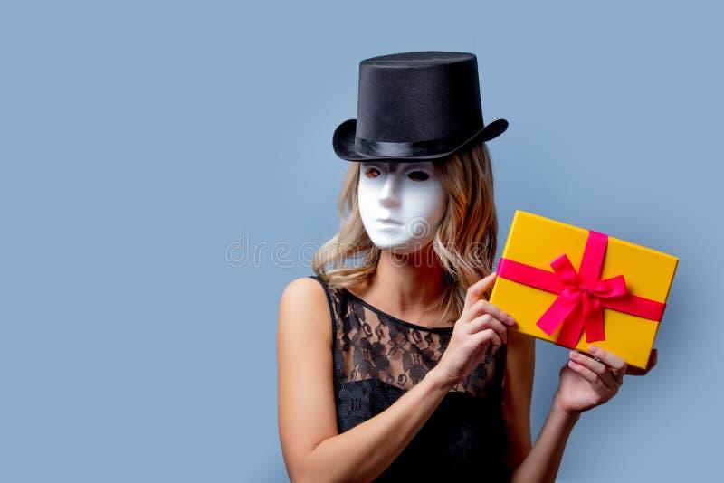 Девушка в верхней шляпе и белая маска с подарочной коробкой стоковые изображения rf