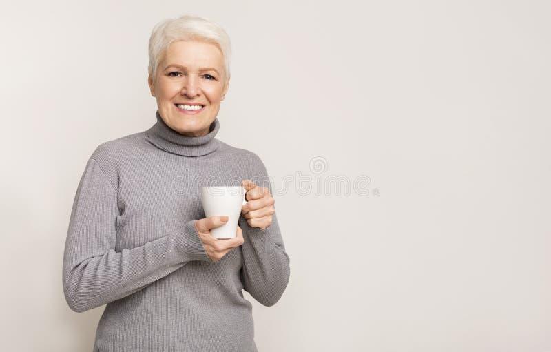 Девушка в возрасте с чашкой с горячим напитком пытается согреться стоковые изображения