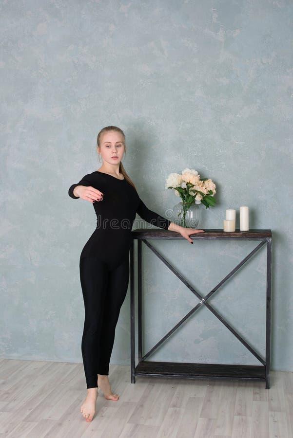 Девушка в гимнастических одеждах танцует на таблице с цветками, свечами стоковые фото