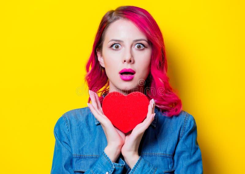 Девушка в голубой рубашке держа красную коробку формы сердца стоковое изображение rf