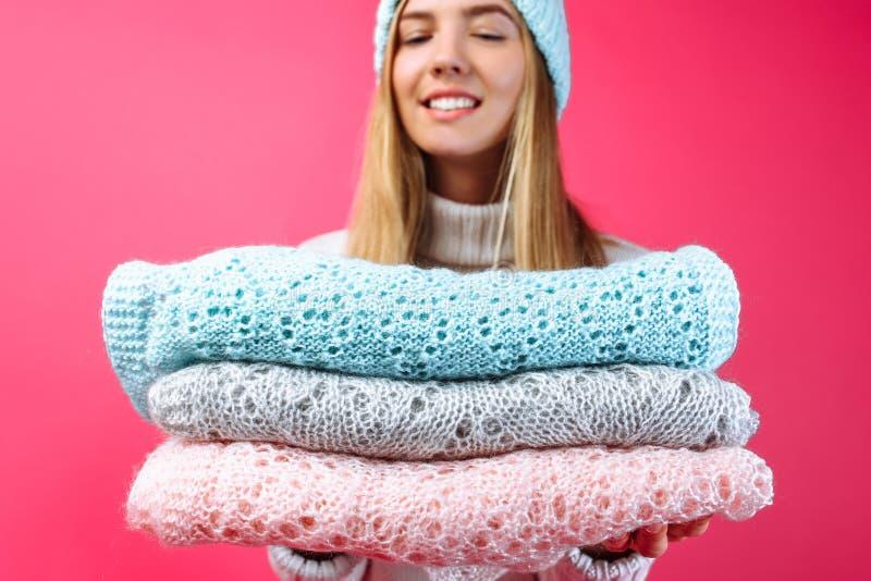 Девушка в голубой теплой шляпе, держа шарфы на красном backgrou стоковые изображения