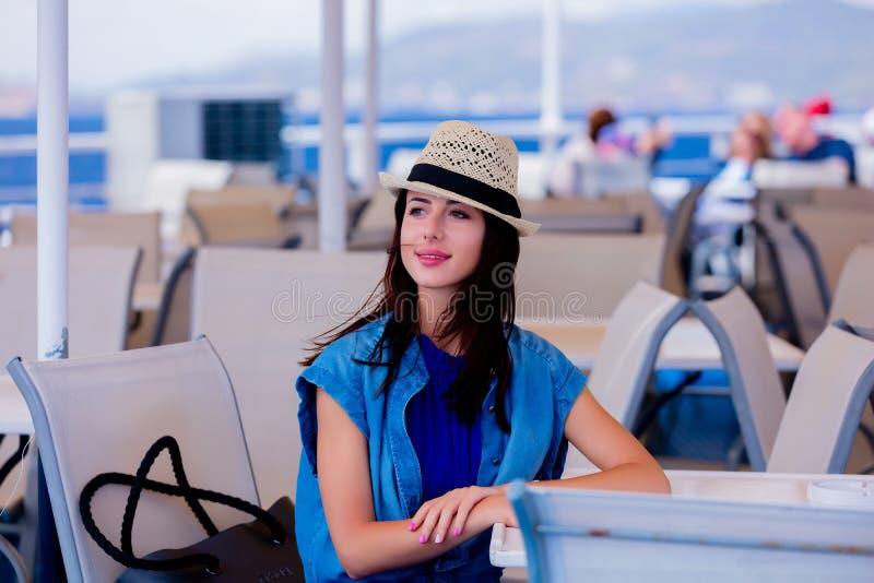 Девушка в голубом платье и шляпа имеют рейс на шлюпке стоковое изображение