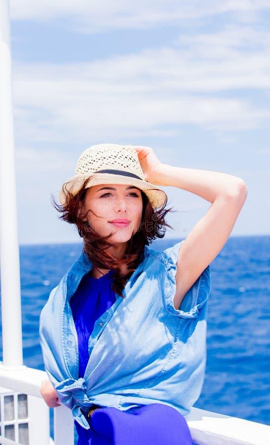 Девушка в голубом платье и шляпа имеют рейс на шлюпке стоковые изображения rf