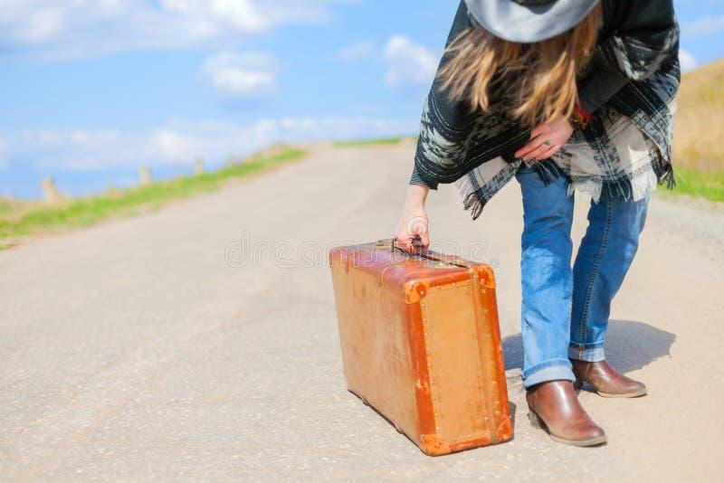 Девушка в голубых джинсах, плащпалата, черная кожаная шляпа с старым коричневым чемоданом в ее руках на дороге стоковое фото rf