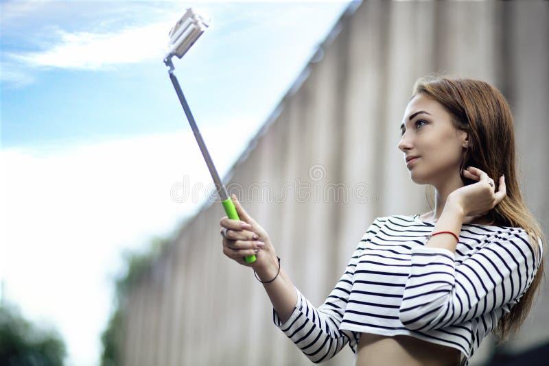 Девушка в городе представляя к смартфону, молодая женщина делая selfie для социальной сети, образа жизни подростка концепции стоковое изображение rf
