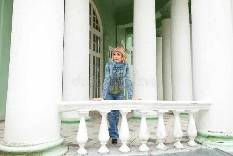Девушка в городской джинсовой ткани около белой балюстрады стоковые фотографии rf