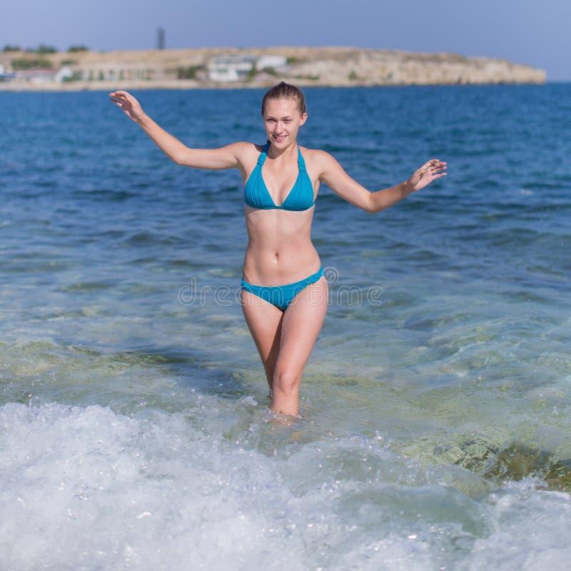 Девушка в голубом бикини приходит от морской воды стоковые фото