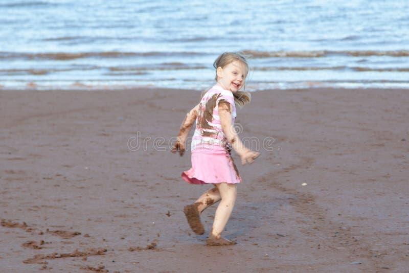 Девушка в грязи на пляже стоковые фото